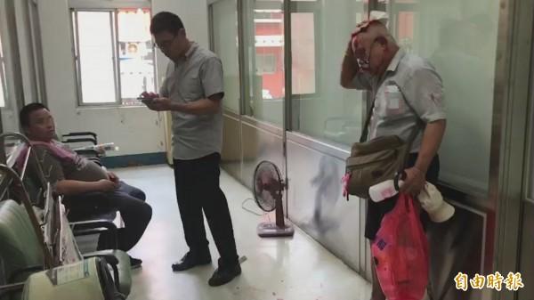 打人的曾男坐在椅子上接受警方初步訊問,受傷的薛男則拿著衛生紙先止血。(資料照,記者吳昇儒翻攝)