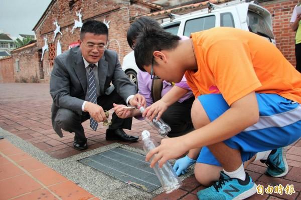 學生現場示範撿菸蒂,鎮長黃振彥大讚做了維護古蹟街景乾淨最好示範。(記者張聰秋攝)