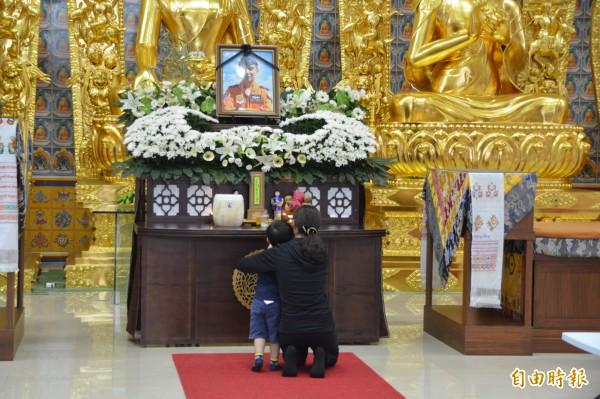 殉職飛官吳彥霆少校的妻子及兒子在靈堂前祭祀。(記者王峻祺攝)