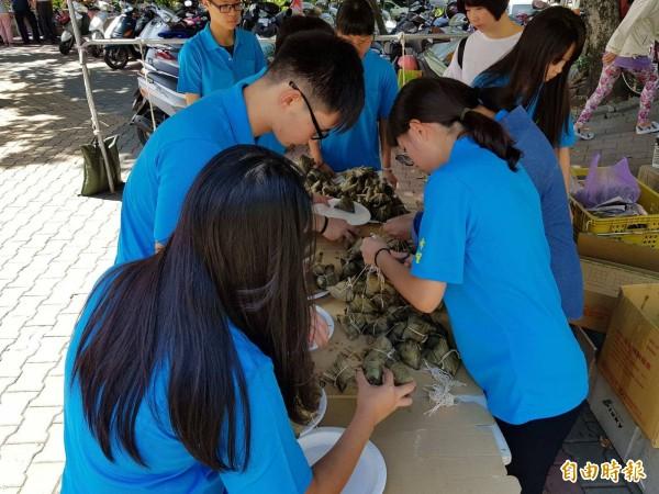 台東縣希望關懷協會包粽活動中,有不少高中應屆畢業生來幫忙。(記者王秀亭攝)