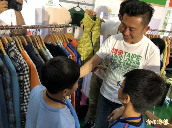 林智堅今天也化身為公益大使,替現場孩童挑選衣物,象徵他將市府匯集的愛,遞送予轄內的家戶。(記者王駿杰攝)