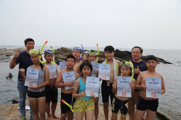 基隆市中華國小舉辦浮潛畢典,學生在水中領取畢業證書,上岸後,畢業生開心地合影留念。(圖由中華國小提供)