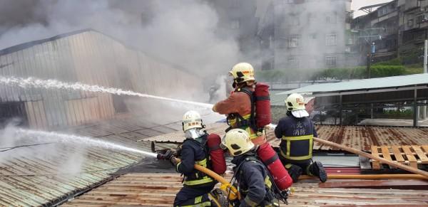 新北市板橋一間紙類裝訂工廠大火全面燃燒,消防員射水灌救。(記者吳仁捷攝)