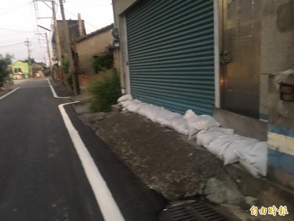 擔心淹水民眾在住家門口堆置沙包。(記者黃淑莉攝)