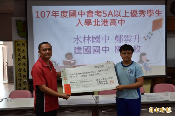 北港高中文教基金會董事吳芳林頒發入學獎學金給鄭雲升。(記者黃淑莉攝)