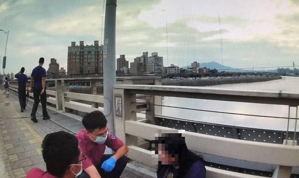 警消趕扺發現38歲何女坐在橋上人行道,士林警方和消防救護人員輪番上陣勸說。(警方提供)