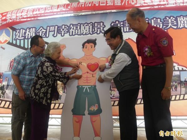 金三榮建設董事長陳含英(左二)與金門縣副縣長吳成典(右二),共同將AED貼片貼在模型身上。(記者吳正庭攝)