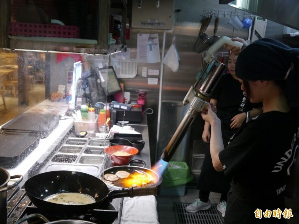 炎神台中麗寶店張姓女主廚以火焰烹飪方法製作拉麵。(記者張軒哲攝)