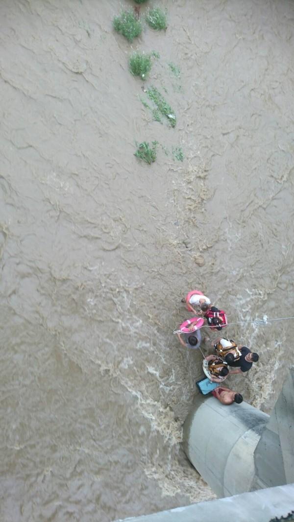 新北市大豹溪今天下午溪水暴漲,7人受困金龍橋,消防員到場緊急救援。(記者吳仁捷翻攝)