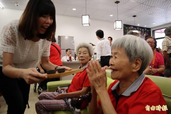 立委洪慈庸為老人奉茶,逗得老人十分開心。(記者歐素美攝)