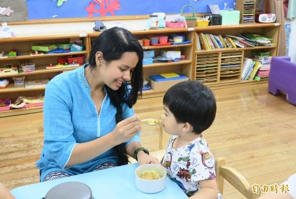凱瑟琳協助光明早療小朋友用餐。(記者蔡文居攝)