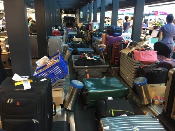 桃園機場二期航廈出境行李自動分揀系統北側輸送系統頻頻故障,造成旅客出境行李「卡關」,旅客和航空公司抱怨連連,報到島櫃輸送帶塞滿行李,動彈不得。(旅客提供)