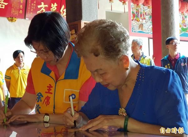 台北市長柯文哲的媽媽何瑞英(右)今天陪同民國黨主席、新竹縣長參選人徐欣瑩(左)到廣和宮參拜後,2人虔誠填寫祈福卡。(記者蔡孟尚攝)