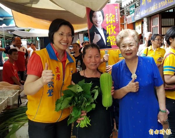 台北市長柯文哲的媽媽何瑞英(前排右)今天陪同民國黨主席、新竹縣長參選人徐欣瑩(前排左)到新竹縣新埔市場掃街拜票,不少民眾熱情送菜表達支持。(記者蔡孟尚攝)
