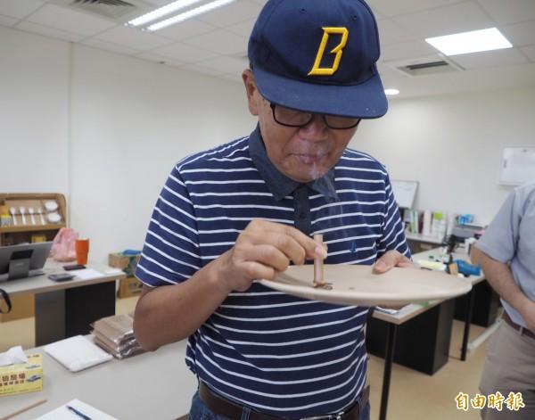 謝志誠教授試驗甘蔗纖管吸管焚燒後,產生的碳化反應。(記者陳鳳麗攝)