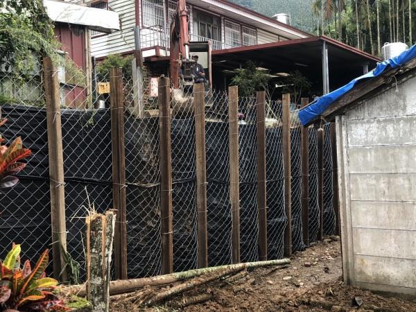 仁愛鄉中正村崩塌邊坡已緊急以鋼軌樁、鐵網、不透水布及填土穩固。(記者佟振國攝)
