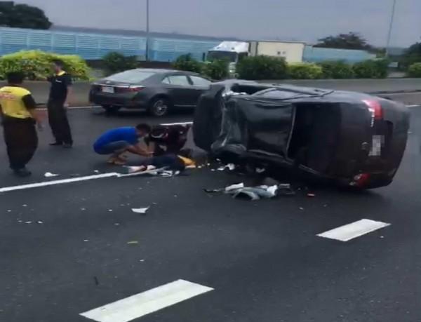 吳女開車行經國道1號時疑為了撿早餐,轎車失控撞護欄側翻,被救出躺國道待援。(記者湯世名翻攝)