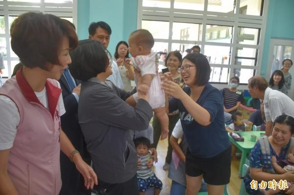 蔡英文首先至托育中心與嬰兒互動。(記者邱灝唐攝)