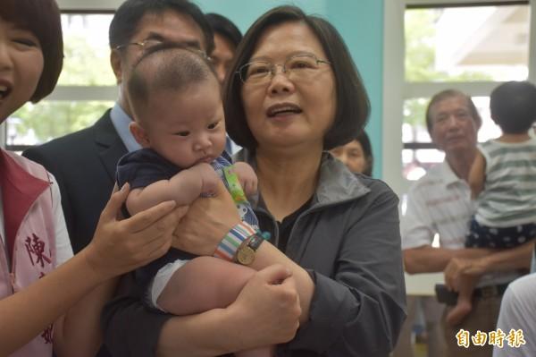 蔡英文到托育中心抱起嬰兒。(記者邱灝唐攝)