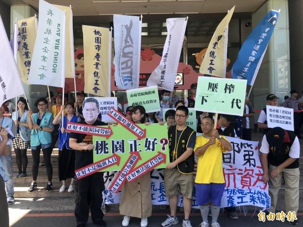 近廿名工會成員高舉旗幟、標語、拉白布,並以熱門的世足賽行動劇,表達不滿與抗議。(記者魏瑾筠攝)
