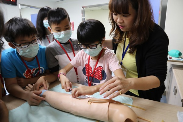 學童利用擬真病人體驗抽血。(圖:興大提供)