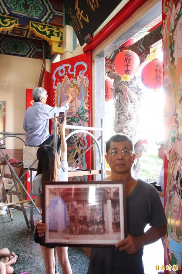彩繪名家蔡龍進為門神「開面」,展現「四方眼」畫技,主委黃慶如展示老照片。(記者林宜樟攝)