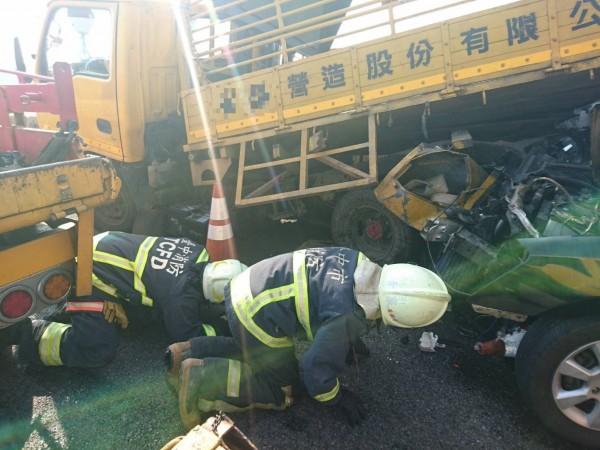轎車追撞停放路肩的工程車意外,警消救援卡在車底工人。(記者張軒哲翻攝)