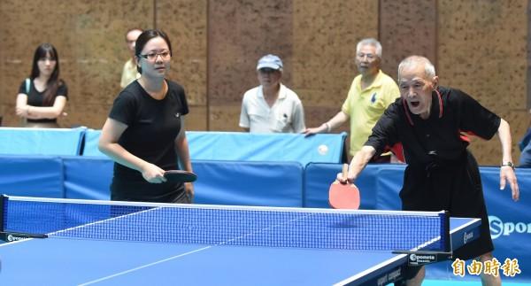2018富邦甲子盃桌球賽28日在台北車站大廳舉行,其中年紀最長的89歲涂世龍(右)報名百歲混雙組賽事,與球友一起來活躍走動,在比賽中感受熱情和活力。(記者劉信德攝)