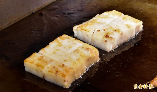 煎至焦黃的手工蘿蔔糕口感Q軟,還有濃濃菜頭味,配上特製辣椒醬、甜辣醬,是店內的人氣商品。(記者張議晨攝)
