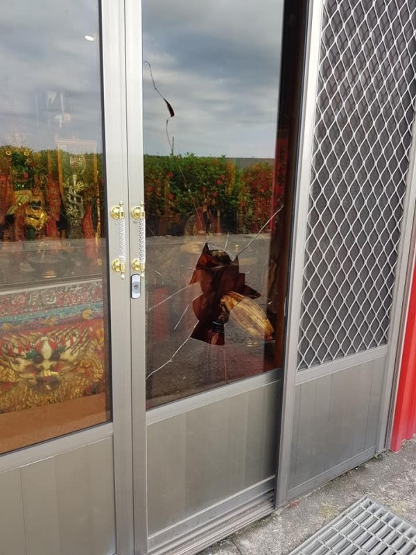 竊賊用石塊將寺壇落地鋁門窗玻璃丟破,入內行竊金牌。(翻攝自「爆料公社」)