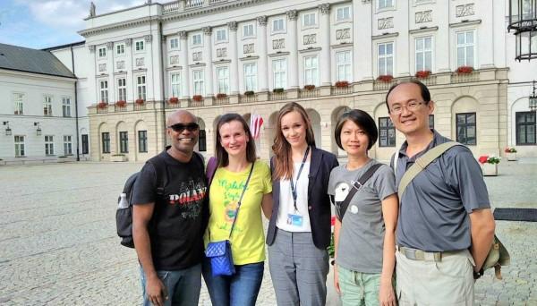 南投市平和國小英文老師李宏哲夫婦(右1、2),在波蘭旅遊時與波蘭總統府人員一起開心合照。(李宏哲提供)
