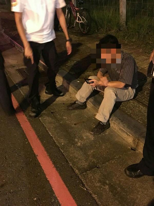 李男酒駕失控撞安全島,車子翻覆,他全身酒味爬出車子,呆坐在路旁。(記者方志賢翻攝)