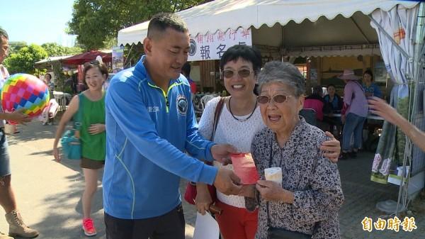 阿嬤金吳瑞琳創下台東最高齡體驗飛行傘的紀錄,業者(左)貼心包個紅包給阿嬤。(記者王秀亭攝)