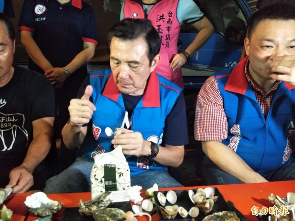 馬英九(中)到台南武聖夜市陪市長參選人高思博(右)拜票,坐下來品嚐烤蚵仔、烤蛤仔,豎起拇指直說太棒了。(記者邱灝唐攝)