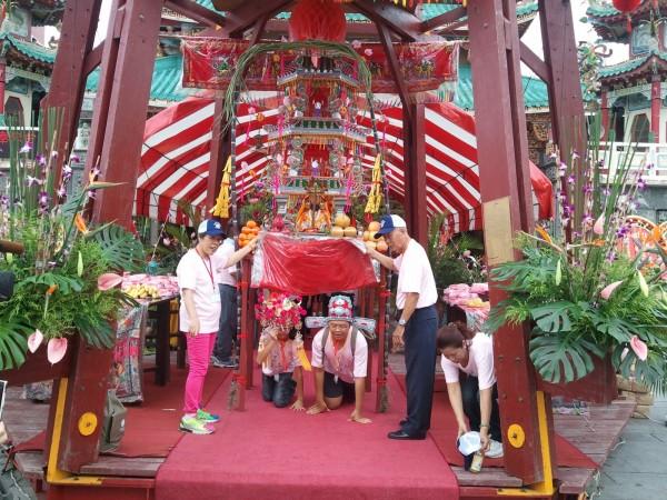 學子鑽過七娘媽亭,進行「出鳥母宮」儀式。(區公所提供)