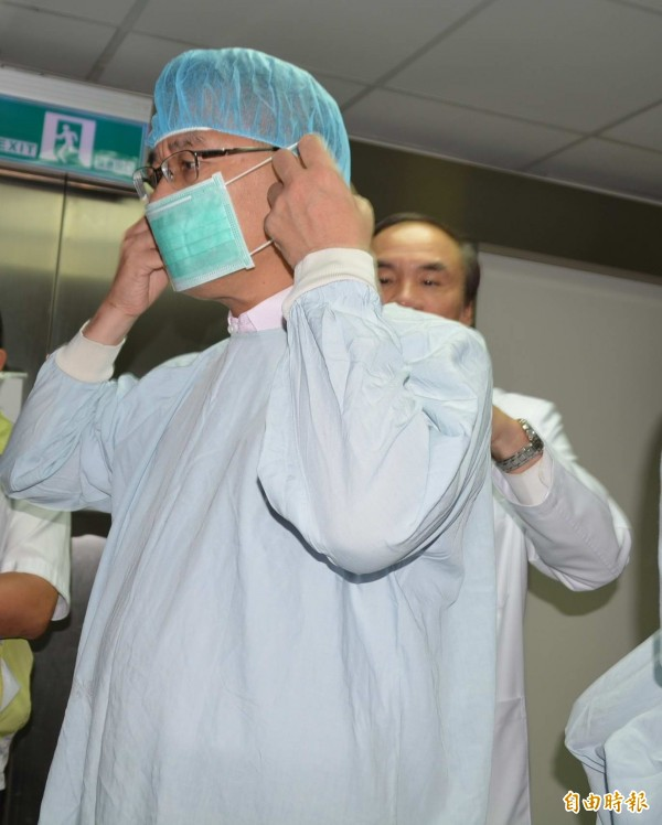 內政部長徐國勇前往探視遭撞傷的女警吳芳如,穿戴隔離衣進入加護病房。(記者湯世名攝)