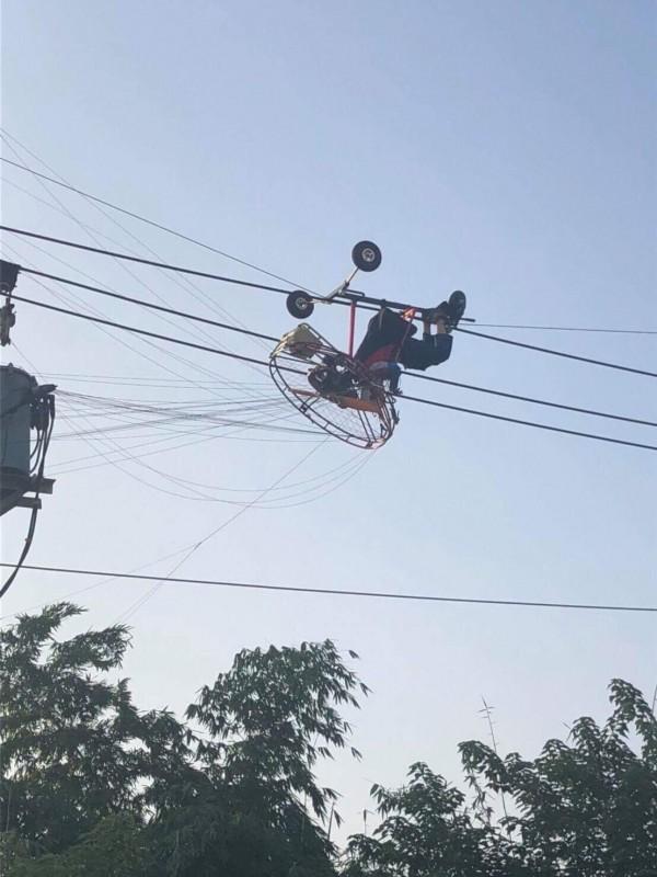 烏日發生一名玩飛行傘的男子被困在電線上,警消獲報立即救援,民眾出借吊車協助脫困,幸無大礙。(記者蘇金鳳翻攝)