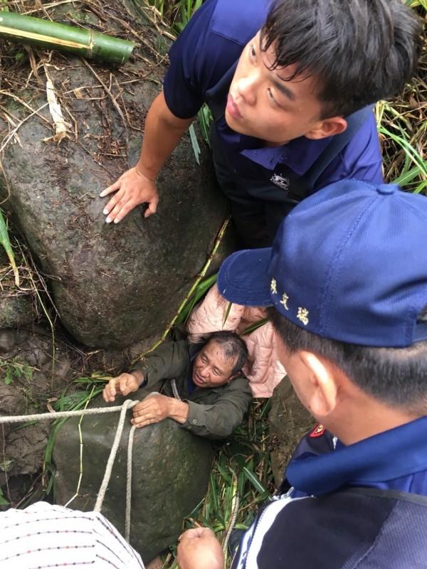 葉姓釣客被石頭壓住,救援人員救援中。(記者蔡宗勳翻攝)
