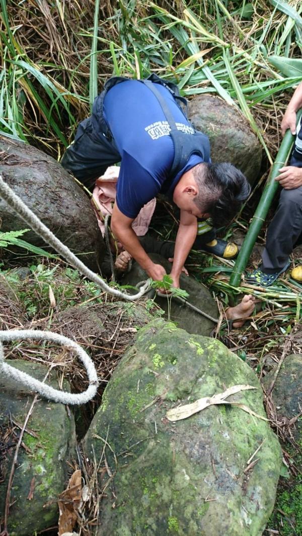 葉姓釣客被頭壓住,救援人員用繩索綁住石頭救援。(記者蔡宗勳翻攝)