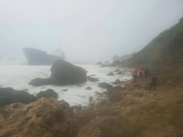 擱淺在柴山鬼洞前的「昌龍68號」輪船(左),海巡署第五岸巡總隊派員警戒(右)。(記者洪定宏翻攝)