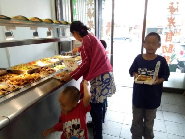 陳婦帶3個小兒去自助餐包便當,平常捨不得買太多菜的陳婦剛領到善款,「每個便當都夾大雞腿、香腸、白帶魚3個主菜」,老闆娘只收260元,還奉送5公斤大包白米。(柯千惠提供)