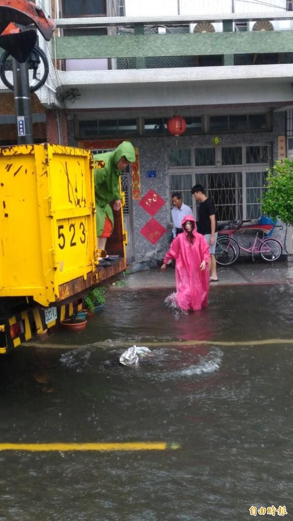 南州萬華村水患依舊,鄉代劉美吟幫忙搬沙包給居民擋水。(記者陳彥廷攝)