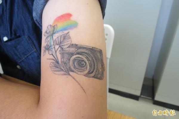 陳映汝選擇哥哥陳冠齊最常用的相機及在彩虹下綻放的紫荊花圖案,刺青展思念。(記者蘇孟娟攝)