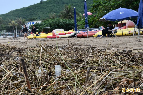 南灣沙灘狀況慘,遊客休憩畫面詭異。(記者蔡宗憲攝)