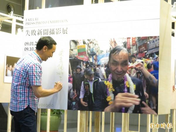 新北市長朱立倫在潑水節被潑得全身濕、狼狽不已的照片,獲得失敗新聞攝影展的第一名,朱立倫出席展覽並在照片旁簽名。(記者何玉華攝)