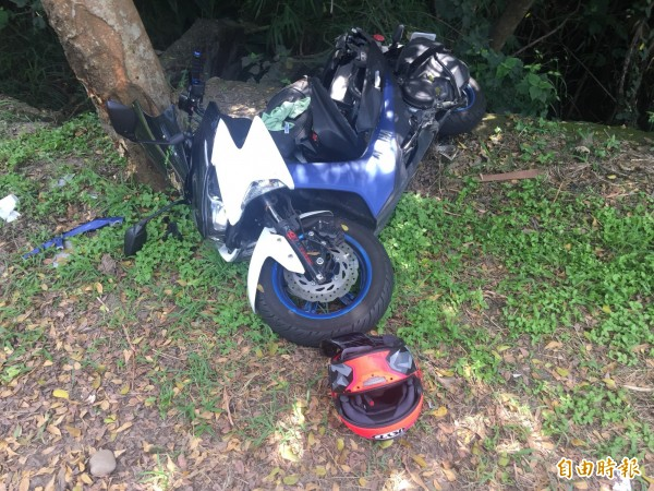 吳姓少年騎乘的機車衝撞路樹,嚴重毀損,安全帽則噴飛。(記者湯世名攝)