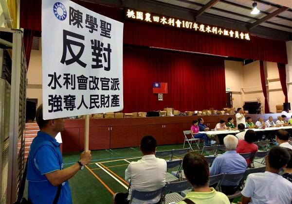 鄭文燦致詞時,陳學聖團隊帶來「反對水利會改官派、強奪人民財產」的立牌仍高舉。(陳學聖服務處提供)