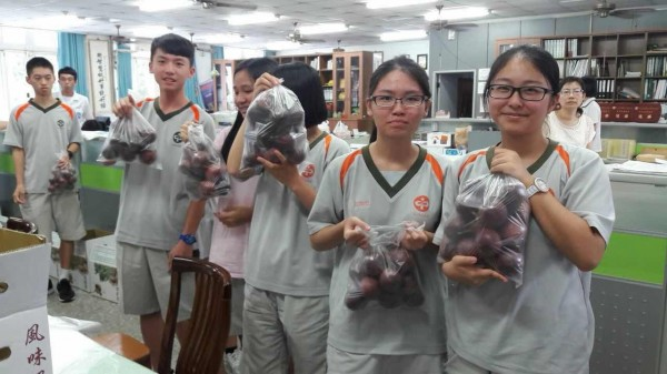各班同學領取農民愛心贈送的百香果當飯後水果。(暨大附中提供)