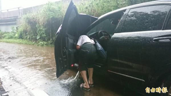駕駛打開車門,拿取必需用品。(記者吳昇儒攝)