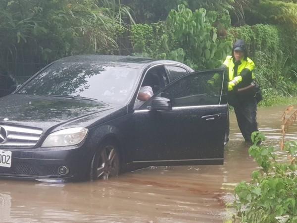 警方與駕駛幫忙讓車子脫困。(記者吳昇儒翻攝)